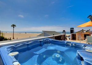 a hot tub on a rooftop deck overlooking the ocean